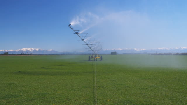 ws irrigation machine rotating over paddock and spraying water / ashburton, canterbury, new zealand - sprinkler system stock videos & royalty-free footage