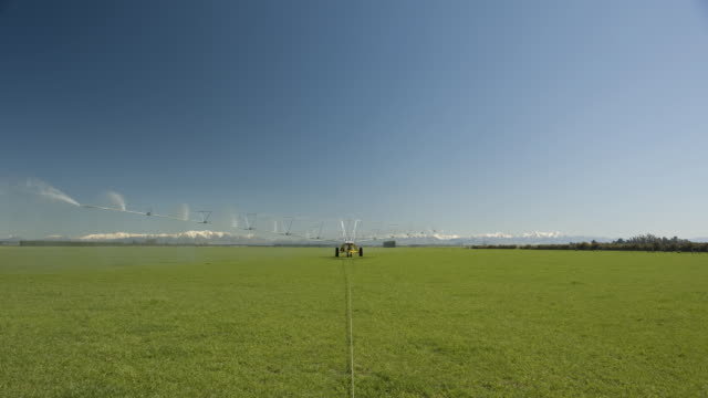 t/l ws irrigation machine rotating over paddock and spraying water / cromwell, central otago, new zealand - bewässerungsanlage stock-videos und b-roll-filmmaterial