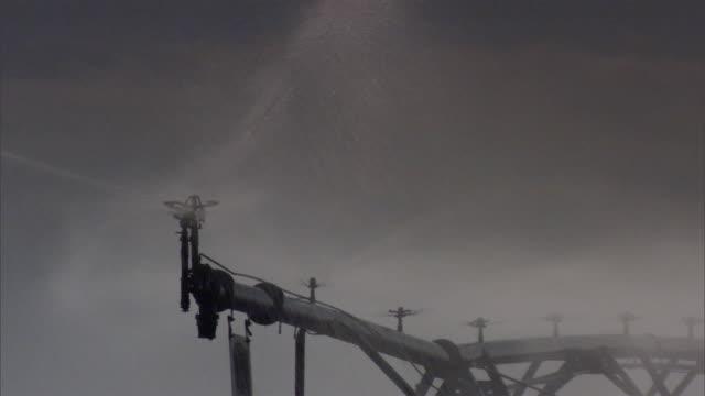 ms cu pan  irrigation rig sprinkling in field  / usa  - sprinkler stock videos and b-roll footage