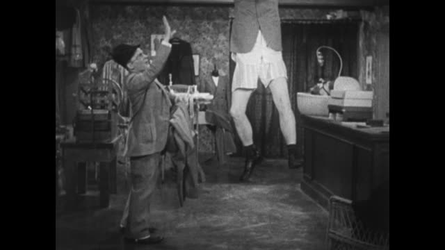 1934 irritable customer grabs trapeze on tailor shop ceiling for pant removal by salesman - 1934 stock videos & royalty-free footage