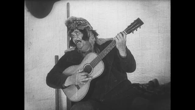 1922 irritable man (buster keaton) commands man to play music before falling through igloo wall - igloo stock videos & royalty-free footage