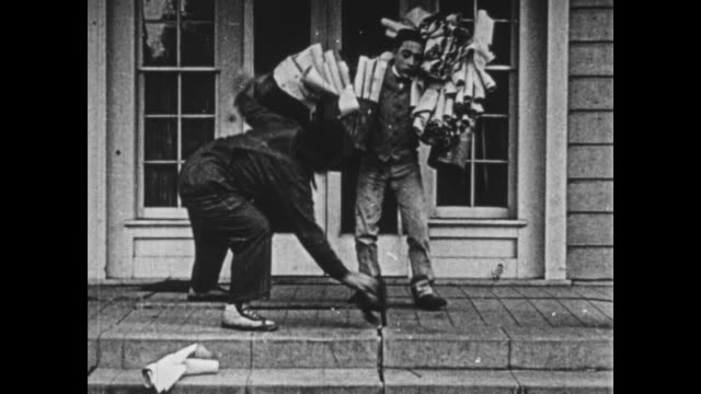 vidéos et rushes de 1925 irritable man (oliver hardy) knocks down wide eyed helper, who bangs into door while carrying rolls of wallpaper - hôpital psychiatrique