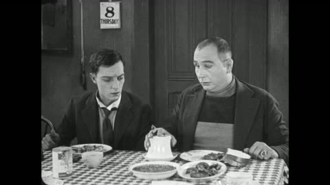 1922 irritated man (buster keaton) pours coffee into full sugar bowl to surprise of dinner guest who pokes himself in eye with spoon - slapstick comedy stock videos & royalty-free footage
