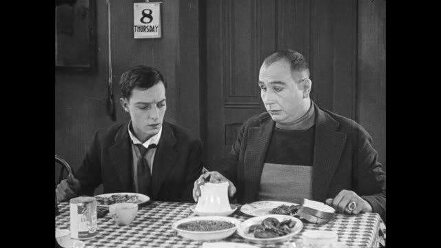 stockvideo's en b-roll-footage met 1922 irritated man (buster keaton) pours coffee into full sugar bowl to surprise of dinner guest who pokes himself in eye with spoon - versmelten
