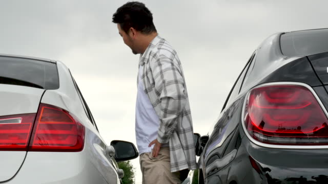 irritated middle-aged man opening door carefully to avoid door ding - ajar stock videos & royalty-free footage