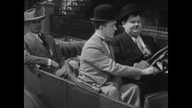 1931 irritated oliver hardy smacks away stan laurel's hand as they drive down the road - oliver hardy stock videos & royalty-free footage