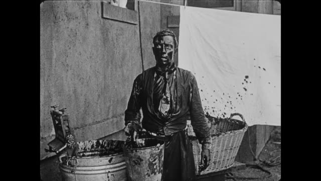 1920 irritated painter kicks bucket of paint on resigned man's (buster keaton) head before policeman (eddie cline) shows up and escorts man from scene - 無声映画点の映像素材/bロール