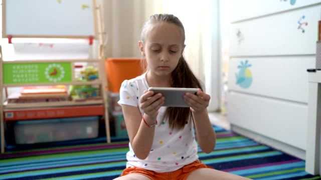 irritated young girl watching on her phone and frowning at camera - refusing stock videos & royalty-free footage