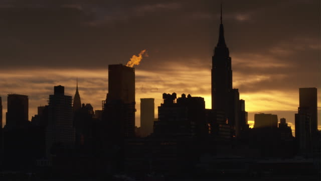 nyc is in silhouette early morning as the golden sun prepares to rise behind the buildings.  steam rises off a skyscraper and the empire states building is featured. - 気まぐれな空点の映像素材/bロール
