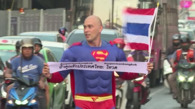 Is it a bird Is it a plane No it's Superman running through Bangkok's heavy traffic with a Thai flag and banner urging people to vote in Sunday's...