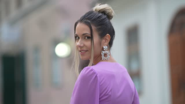 isabela francesca wears bejeweled earrings, a pastel purple low-neck cropped top with oversized long flared flowing sleeves, matching pastel purple... - ponytail stock videos & royalty-free footage
