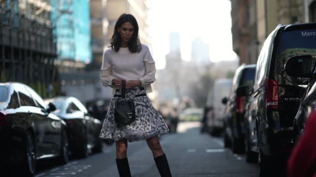 Isabella Charlotta Poppius wears a pleated floral print skirt a black leather bag a white wool top over a shirt black high boots during London...
