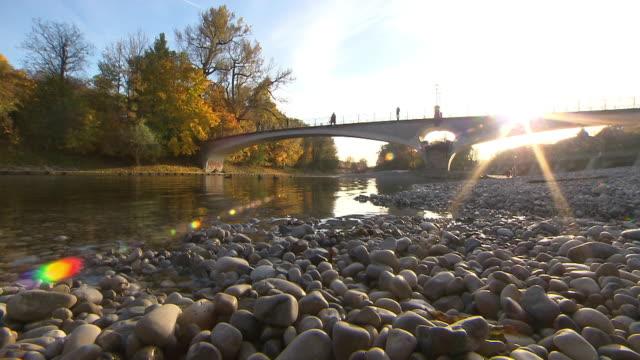 isar, river, water, stones, autumn, bridge, people, coloured trees - gruppo medio di animali video stock e b–roll