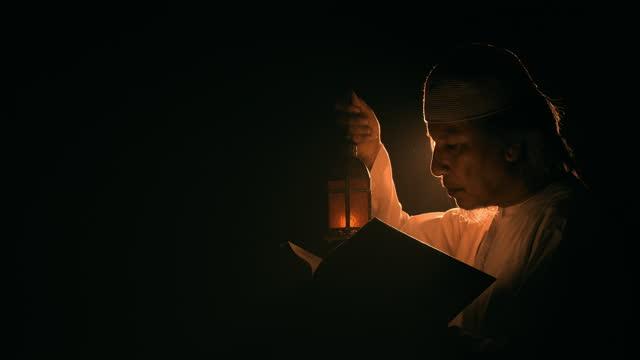 islam man reading muslim bible, koran, back lit, medium shot, thinking and flipping page, lantern. - one mid adult man only stock videos & royalty-free footage