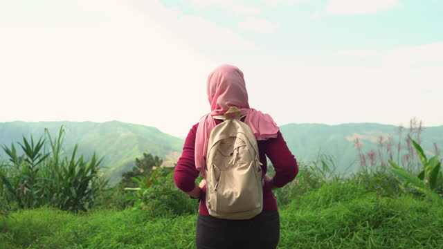 islam southeast asian mid woman with a religious dress, hijab, and backpacker standing, looking at a view of a mountain range with feeling happiness, relaxation, enjoyment. concept of muslim travel, hobby, loving adventure, explorer and alone at nature. - religious dress stock videos & royalty-free footage