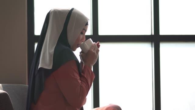 islam woman is drinking hot tea or coffee - coffee drink stock videos & royalty-free footage