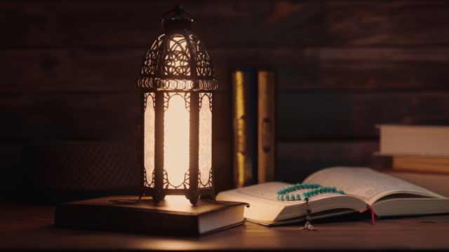 islamic concept - the holy al quran with written arabic calligraphy meaning of al quran and a beautiful arabian lamp, arabic word translation: the holy al quran (holy book of muslim) - spirituality stock videos & royalty-free footage
