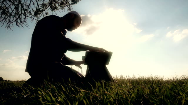 Islamic Man Reading Quran In The Grass