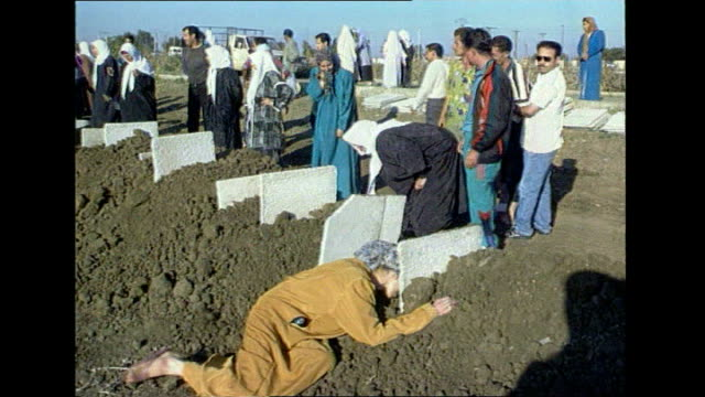 Islamic militancy on the rise in Africa LIB Orig TX ALGERIA Algiers EXT Civilians crying at mass grave site Civilians by graves as one woman falls...