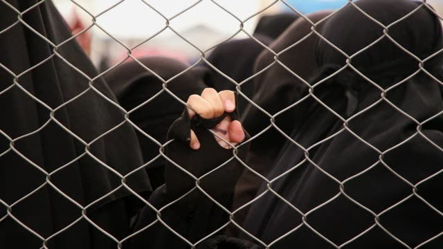 vídeos y material grabado en eventos de stock de islamic state supporters women wearing burka's kept fenced up at al hawl internment camp in syria after the collapse of is - valla límite