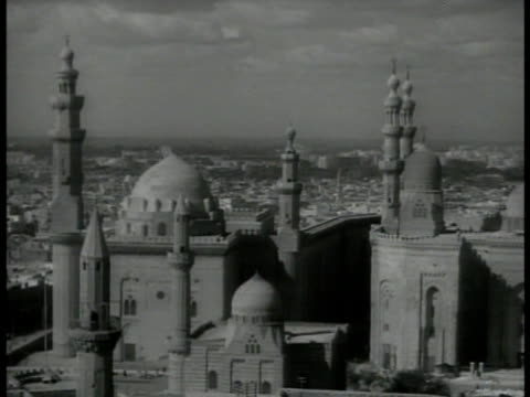 Islamic temple HA MS Temple spires WS Arabs walking down parade on street HA WS Arabs parading HA XWS Crowded Arab market camels FG WS Temples WS...