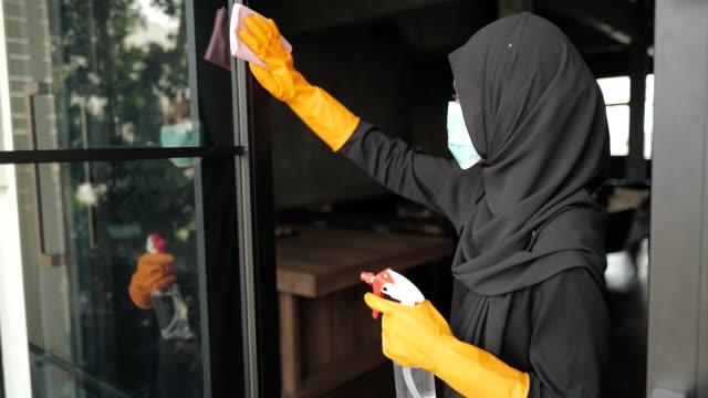 islamic woman disinfecting glass window - モデスト・ファッション点の映像素材/bロール
