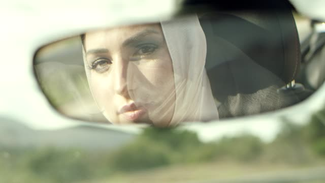 islamic woman driving car. inside car mirror portrait - only women stock videos & royalty-free footage