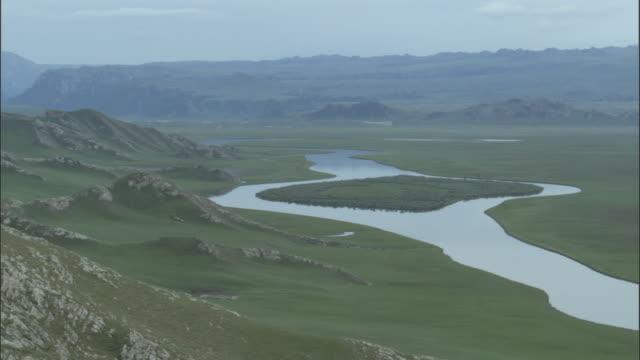 Island in middle of river meandering through grasslands, Bayanbulak grasslands.