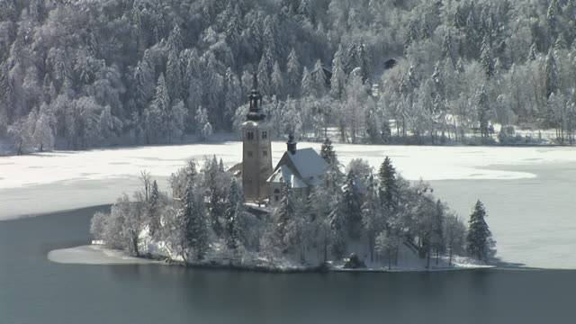 ws, ha, island on lake bled with church of the assumption of mary surrounded with snow covered trees, gorenjska, slovenia - lago di bled video stock e b–roll