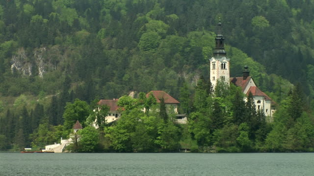 ms, island on lake bled with church of the assumption of mary surrounded with trees, gorenjska, slovenia - lago di bled video stock e b–roll