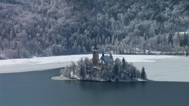 ha, zo, ws, island on lake bled with church of the assumption of mary surrounded with snow covered trees, gorenjska, slovenia - circa 15th century stock videos & royalty-free footage