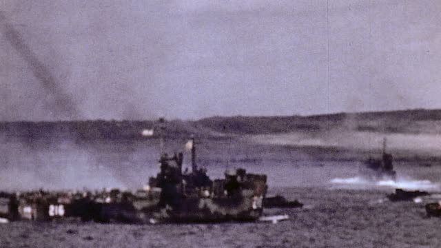island shoreline smoking from bombardment and many invasion craft and warships offshore / iwo jima japan - battle of iwo jima stock videos and b-roll footage