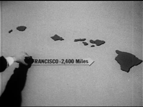 vidéos et rushes de island silhouette cutouts male hand placing arrow mile marker sign near islands 'san francisco 2400 miles' 'tokyo 3850 miles' - 1953