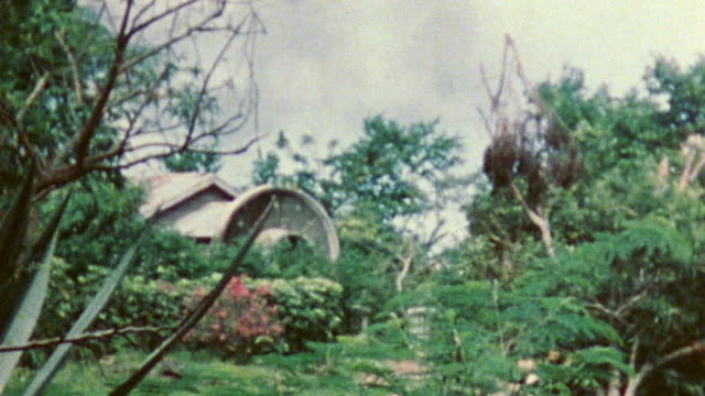 island village buildings bamboo wood pile and encroaching jungle with us marine walking toward freestanding watchtower during wwii / tinian mariana... - infanterie stock-videos und b-roll-filmmaterial