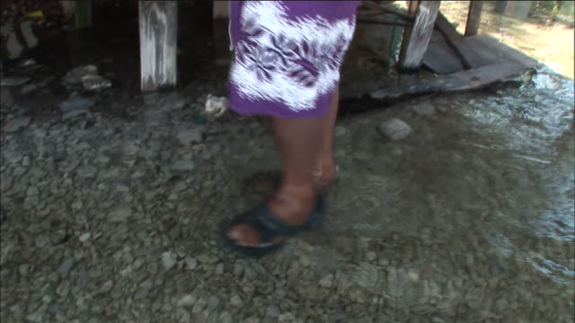 islander wades through flood water beside village market stalls tuvalu - パレオ点の映像素材/bロール