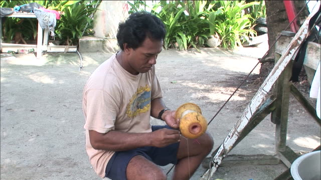 Islander winds away fishing line in shade of palm trees Funafuti Tuvalu