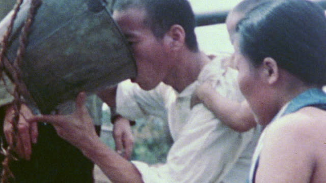 stockvideo's en b-roll-footage met islanders drinking well water from a bucket and villager crouching on the ground washing his hair from a basin of water during wwii / tinian mariana... - pacifische eilanden