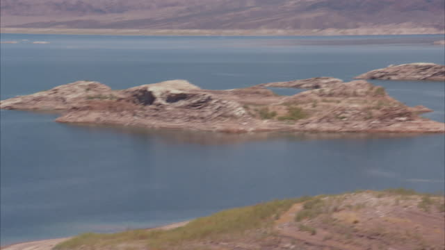 ws pan islands and desert cliffs of lake mead with far shore / lake mead, arizona, usa - lake mead video stock e b–roll