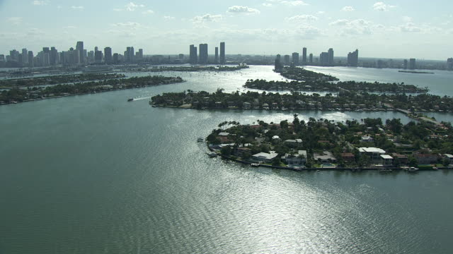 islands in biscayne bay connected by venetian causeway, sunlight reflecting in water, miami skyline skyscrapers & high-rise buildings bg. urban. - biscayne bay stock-videos und b-roll-filmmaterial