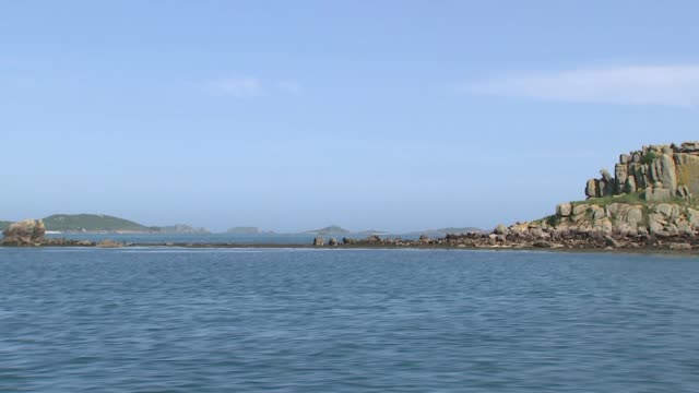 isles of scilly gvs, plants and wildlife; england: cornwall: isles of scilly: ext gvs from small boat looking towards eastern isles/ cormorant flies... - isles of scilly stock videos & royalty-free footage