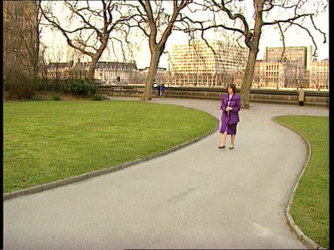 civil action itn lms margaret hodge walking along twds in park pan **bearding on hodge's purple outfit and the tree branches** - マーガレット・ホッジ点の映像素材/bロール