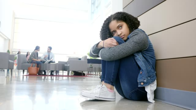 isolated female high school student sits alone in the campus lobby - teenagers only stock videos & royalty-free footage