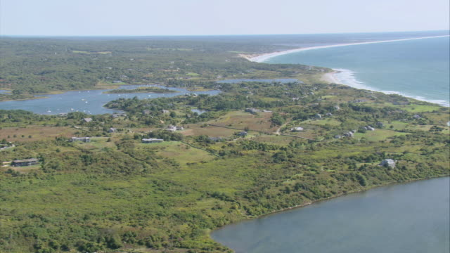 aerial isolated hamlet on island near inlet, with shorelines in front and beyond / aquinnah, massachusetts, united states - inlet stock videos & royalty-free footage