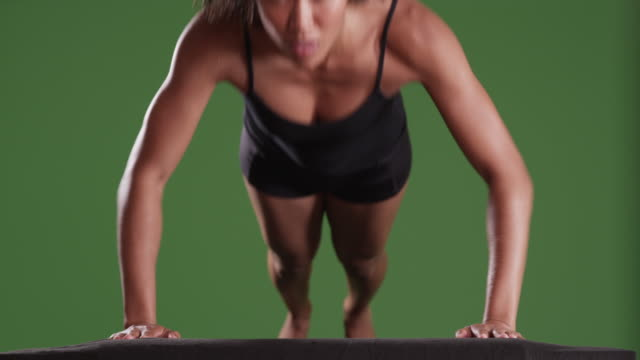isolated mixed race millennial woman athlete doing push ups on green screen - chroma key studio stock videos & royalty-free footage