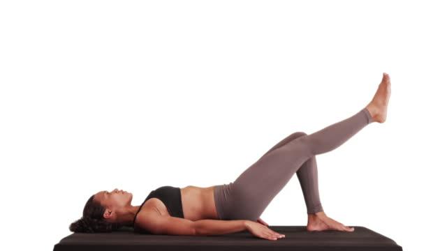 vídeos de stock e filmes b-roll de isolated mixed race woman athlete doing hip raises on matt - ponte