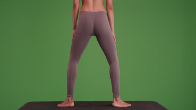 Isolated mixed race woman doing squats on yoga matt on green screen