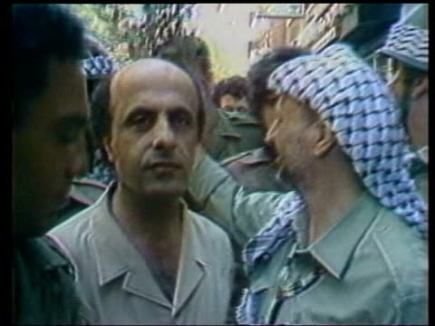 Israel calls for exile of Yasser Arafat LIB LEBANON West Beirut EXT Arafat along surrounded by people as leaving Lebanon Press Arafat sitting reading