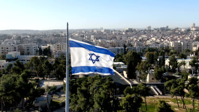 israel flag waving above ammunition hill memorial site/ aerial west jerusalem - israel stock-videos und b-roll-filmmaterial