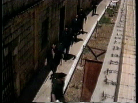 Israel releases prisoners ITN TMS Prisoners walking in line in compound of El Khiam prison camp BV Prisoner through doorway into compound PULL OUT as...