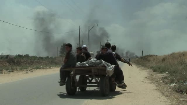 Israeli army open fire on Palestinian protesters ISRAEL / GAZA Men on boys on cart led by donkeys Boys on cart doing peace sign